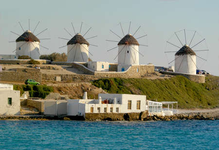 4 Windmills lined up in a row on the island of Mykonos, Greece. The white-washed windmills stand out on this beautiful sunny day with crystal blue skies that are looking over the Aegean Sea. Imagens