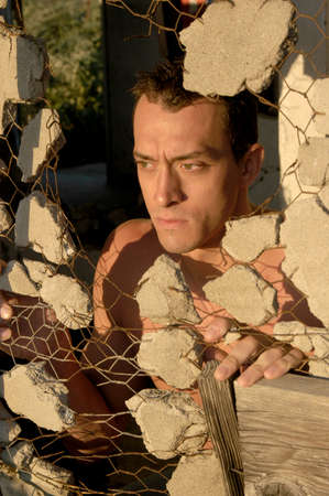 A handsome young man looks through a hole in a broken wall to gaze a the setting sun over farmland.