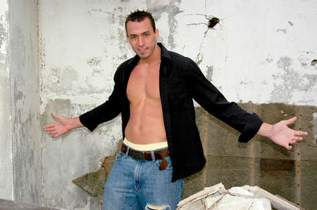 A handsome young man tries out a gangster pose in front of a broken down farm house showing off his muscular chest and abs. Фото со стока