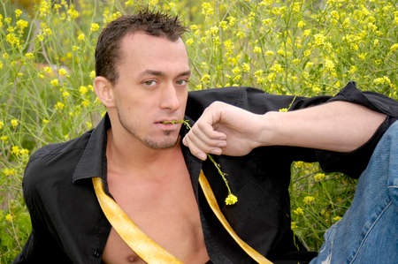 A very attractive muscular young man gives a seductive and sexy look in a field of yellow mustard flowers.