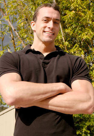 A handsome All American young man stands with his arms crossed to show his muscular arms. 免版税图像