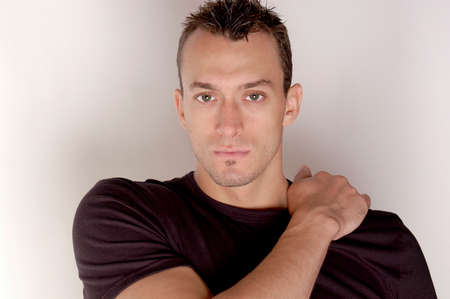 A handsome male model in a studio shoot with a black t-shirt and his arm over his shoulder.