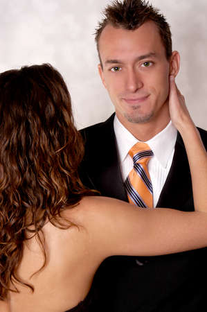 A young handsome office man has a young woman hugging him while he is in his suit with a very happy expression. Stock fotó