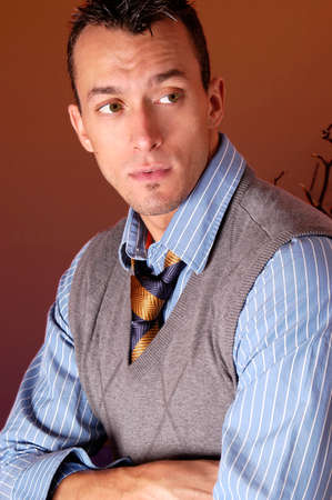 A portrait of a young handsome businessman with a striped shirt and tie looking off to his side.