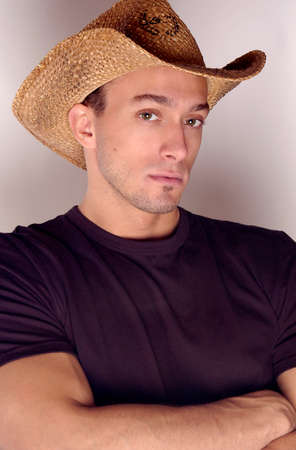 A handsome cowboy in a dark shirt in a studio portrait looking hot and sexy.