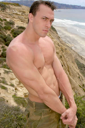 A fit and muscular young man stands shirtless in front of the cliffs overlooking the Pacific Ocean in the background.