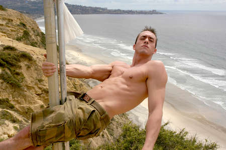 A strong, shirtless, masculine, young man holds on to a pole as he leans over the cliff overlooking the Pacific Ocean in San Diego.