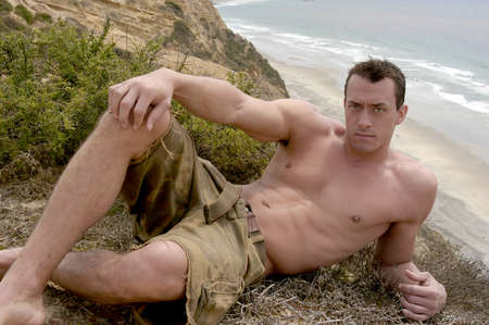 A shirtless and muscular young man lies by the cliff overlooking the Pacific Ocean in San Diego.