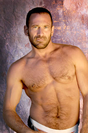 Handsome and muscular man poses for a studio portrait showing that he is in great muscular body. Stock fotó