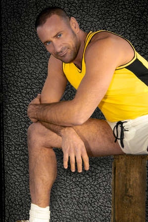 A handsome young and stubble bearded athlete stretches in a relaxed pose for his sport portrait.