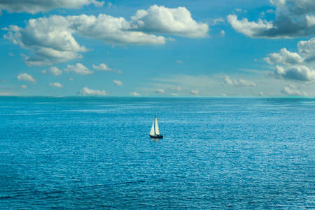 A lone sailboat out in the ocean with a nice breeze and a cloudy but clear sky. 免版税图像
