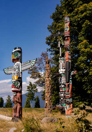 A grouping of four Totem Poles in Vancouver, Canada 免版税图像