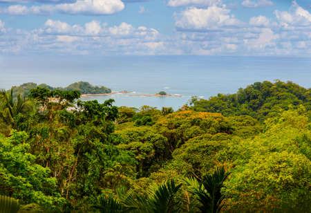 A panoramic view of Dominical Beach in Costa Rica on a mostly sunny day with some puffy white clouds in Central America.
