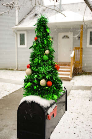A mailbox decorated for the Christmas Holidays with a small Christmas tree.