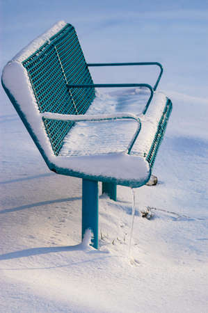 A park bench after a winter's storm covered in snow and ice and looking very cold.