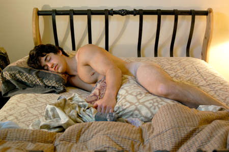 A handsome muscular naked man is sleeping in bed with his eyes close. Stock fotó