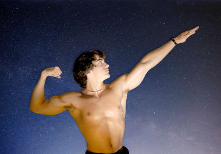 A young, handsome, half-naked man is showing off his muscular body in a classic body-building pose.