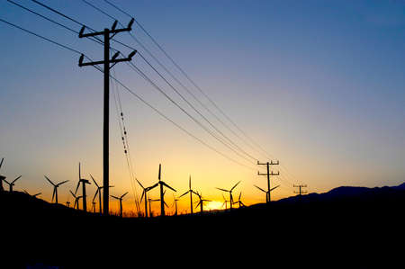 Windmill farm in the desert at sunset in Palm Springs, California with power lines going to the city.