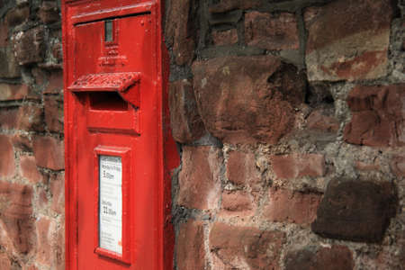 bright red postbox in old crumbling wall - closeup