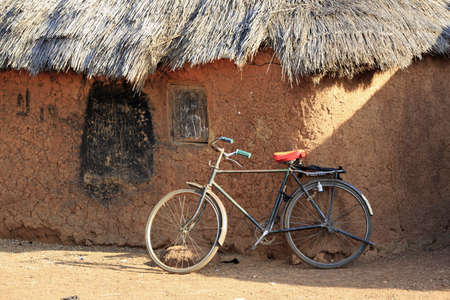thatched house: Mud huts and bike in a traditional African village Stock Photo