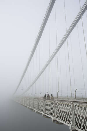 suspension bridge: Group of people contemplating the mist on Clifton Suspension bridge  Stock Photo