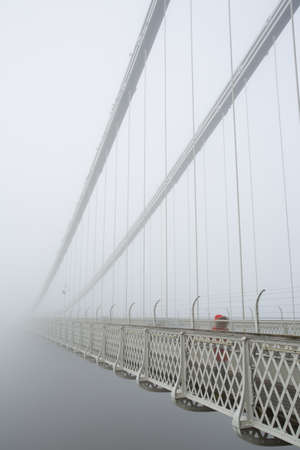 suspension: Person in a red coat coming out of the mist on Clifton Suspension bridge  Stock Photo