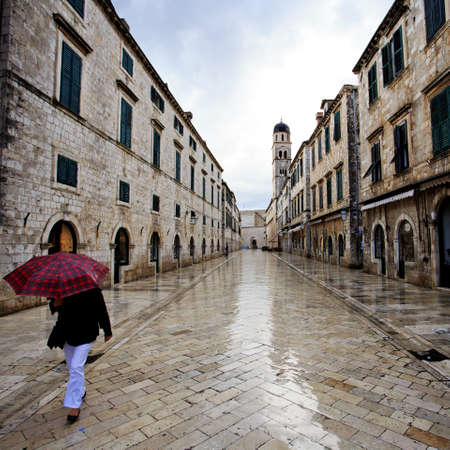 Lady walks through the shiny wet streets at dawn in Dubrovnik photo