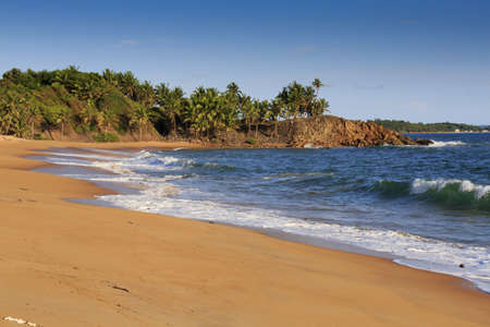Deserted African beach with sand and rocky coastline at sunset in Axim, Ghana Standard-Bild