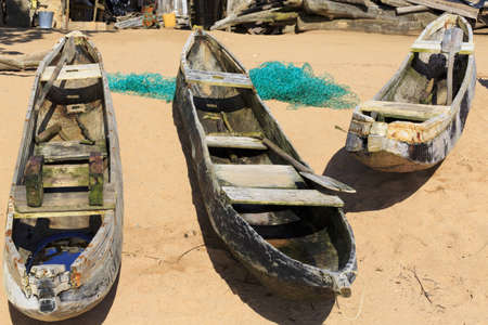 dugout: Three old dugout canoes on the beach with nets in Axim, Ghana