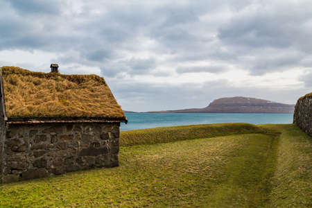 Traditional hut in the Faroe Islands with a green grass roof with a backdrop of the Atlantic ocean and an island Standard-Bild