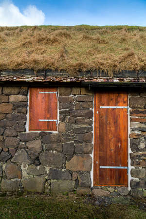 rafters: Facade of a typical rural building with natural grass roof and silver birch rafters in Torshavn Faroe Islands
