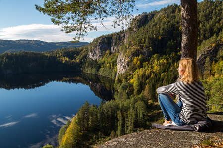 Beautiful young woman contemplating nature on top of a cliff overlooking a beautiful lake Stock Photo