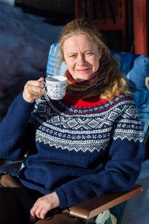 Close up der jungen hübschen norwegischen Frau, die einige Wintersonne und eine Tasse Kaffee in einem traditionellen norwegischen Jumper genießen