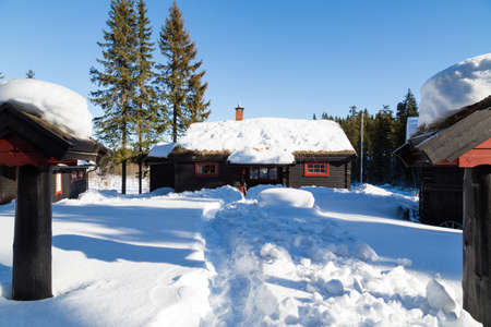 Typical black Norwegian cabin surrounded by deep snow in the forest North of Oslo