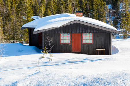 Typical black Norwegian cabin covered in snow in the forest North of Oslo