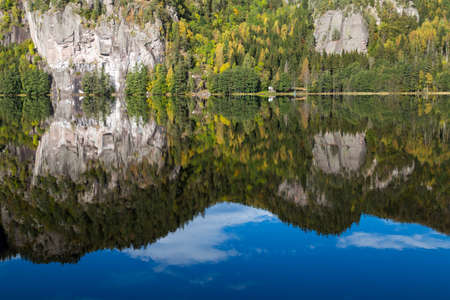 Autumn reflections of a steep cliff in a tranquil lake