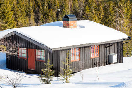 Typical black Norwegian cabin covered in snow in the forest North of Oslo - side view Editorial