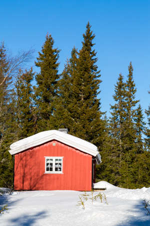 Typical red Norwegian cabin surrounded by snow in the forest North of Oslo Editorial