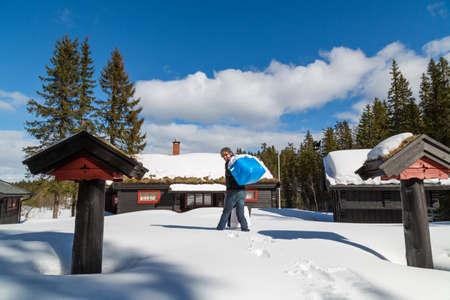 Man-Taschen im tiefen Schnee zu einer traditionellen norwegischen Kabine mitführen Standard-Bild