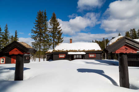 Traditional Norwegian cabin surrounded by deep snow with two pillars with a blue sky