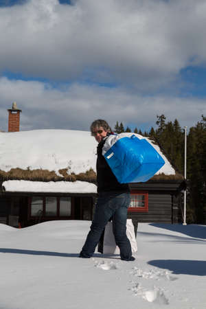 Man carrying bags in deep snow to a traditional Norwegian cabin - portrait