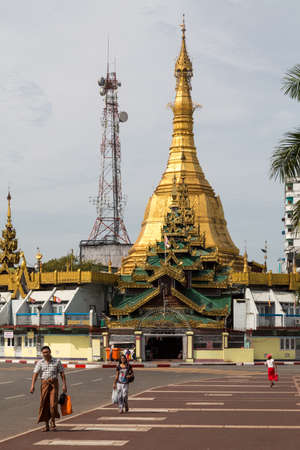 Yangon, Myanmar, 8 Nov 2015. The Sule Paya is positioned in the middle of a roundabout in Yangon, nearby there is a communication mast that almost mirrors the structure