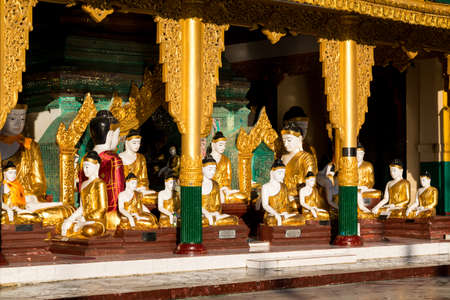 A temple with many different sized Buddhas at the Shwedagon pagoda glisten in the early morning sun in Yangon Editorial