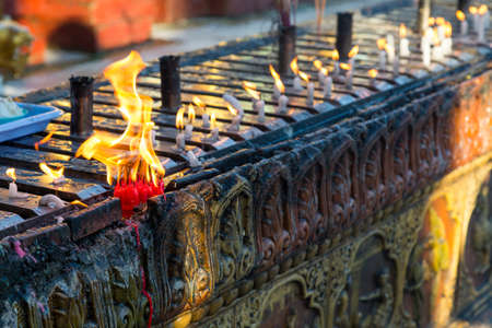 A cluster of candles burning on an carved wall at the Shwedagon pagoda in Yangon