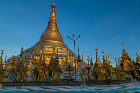 The iconic Shwedagon pagoda glows in a beautiful soft gold light at dawn - landscape Editorial