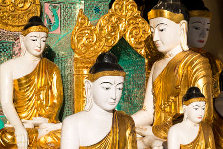 Close up of different sized golden Buddhas at the Shwedagon pagoda in Yangon