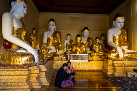 Yangon, Myanmar, 9th November 2015: The Shwedagon pagoda in Yangon embraces people, not just to worship, here two young girls are pictured playing with their smartphones. Myanmar has changed significantly in the last few years since sanctions have been li