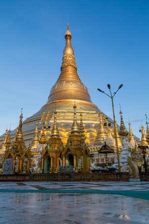 The iconic Shwedagon pagoda glows in a beautiful soft gold light at dawn - portrait Standard-Bild
