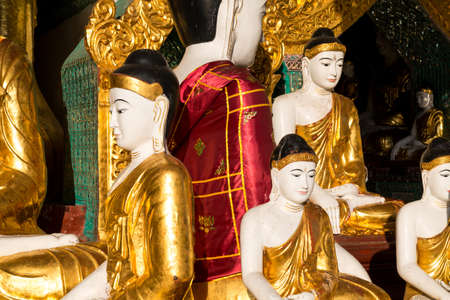 Close up of different sized golden Buddhas, one with a silky red cloak at the Shwedagon pagoda in Yangon