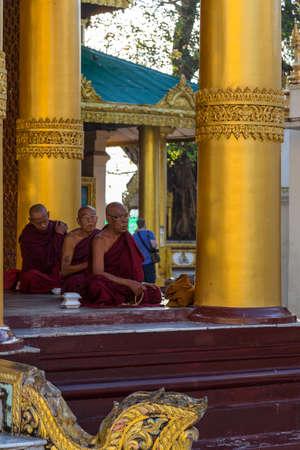 Yangon, Myanmar, 9th November 2015: Three monks pray in a line at the Shwedagon pagoda in Yangon